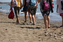 Tourists walking on beach Stock Images