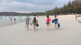 Tourists walking on the beach Royalty Free Stock Images