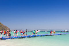 Tourists walking on blue pontoon to the beach at Coral Island  P. PHUKET THAILAND-FEBUARY 21 2016:Tourists walking on blue pontoon to the beach at Coral Island Royalty Free Stock Photo