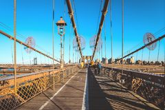 Tourists walking on Brooklyn Bridge in a beautiful day, New York. Full of tourists walking on Brooklyn Bridge in a beautiful day, New York stock images