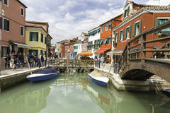 Tourists walking in Burano city streets and boats in the lagoon in beautiful city of Burano Stock Photography
