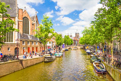 Tourists walking by a canal in Amsterdam. Amsterdam Royalty Free Stock Photo