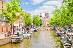 Tourists walking by a canal in Amsterdam Royalty Free Stock Photography