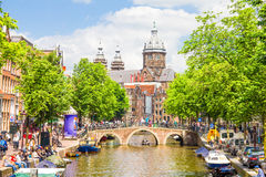 Tourists walking by a canal in Amsterdam Stock Photography