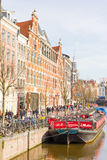 Tourists walking by a canal in Amsterdam Royalty Free Stock Photos