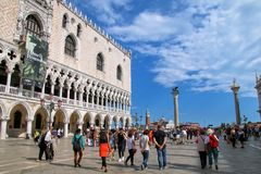 Tourists walking by Doge`s Palace on Piazzetta San Marco in Veni. Ce, Italy. The palace was the residence of the Doge of Venice Royalty Free Stock Photo