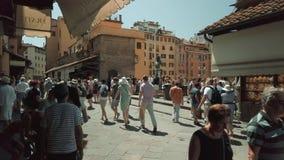 Tourists walking on famous Firenze landmark Ponte Vecchio bridge. Florence, Italy - August 1, 2019: Tourists walking on famous Firenze landmark Ponte Vecchio stock video