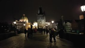 Tourists walking on famous landmark Charles Bridge at night time stock footage