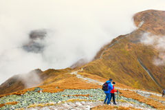 Tourists walking in a foggy day to the top of the Kasprowy Wierch in Tatra Mountains on Octo Stock Photo