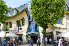 Crooked house. Tourists are walking in front of a crooked house on 26 May 2018 in Sopot, Poland. It was built in 2004 as part of the Resident`s shopping center Stock Image