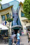 Crooked house. Tourists are walking in front of a crooked house on 26 May 2018 in Sopot, Poland. It was built in 2004 as part of the Resident`s shopping center Royalty Free Stock Photos
