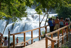 Tourists walking in front of the waterfalls of the Krka Stock Photography