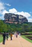 Tourists walking in garden complex with rock of Sigiriya as backdrop Royalty Free Stock Photography