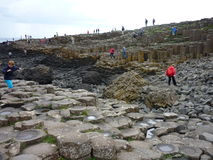 Tourists walking on Giant's Causeway's basalt columns. Giant's Causeway is a popular tourist destination in county Antrim, Northern Ireland. It is an area of royalty free stock photos