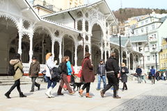 Tourists walking on Market Colonade. Tourists walking in front of summer-house in promenade 'Tržní kolonáda' (Market Colonnade) with medicinal spring in spa Royalty Free Stock Photos