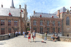 Tourists walking in the narrow streets in the center of Bruges. Bruges is also called the Venice of the North due to the numerous Royalty Free Stock Photo