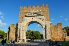 Tourists walking near the ancient arch of Augustus in Rimini, Italy. Rimini, Italy - August 16, 2014: Tourists walking near the ancient arch of Augustus (Arco di Stock Images