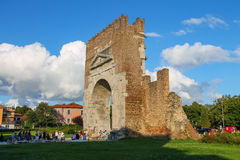 Tourists walking near the ancient arch of Augustus in Rimini, Italy. Rimini, Italy - August 16, 2014: Tourists walking near the ancient arch of Augustus (Arco di Stock Photos
