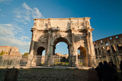 Tourists walking near Constantine's arc in Rome. Triumphal arch in Rome, situated between the Colosseum and the Palatine Hill Royalty Free Stock Image