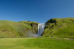 Tourists walking near famous Skogafoss waterfall, South Iceland Stock Image