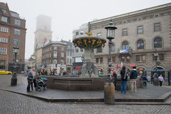 Tourists walking near the fountain of Mercy misty november day. Copenhagen Royalty Free Stock Images