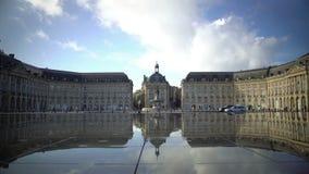 Tourists walking near mirror fountain at Place de la Bourse in Bordeaux, France