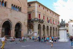 Tourists walking near Rimini City Hall and statue of Pope Paul V Stock Image