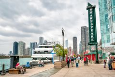 Tourists are walking near Shakespeare theater, located at famous Navy Pier park in Chicago. Chicago, Illinois, USA - April 12, 2012: Tourists are walking near Stock Photos