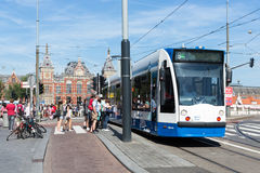 Tourists walking near a tram in Amsterdam Stock Photography