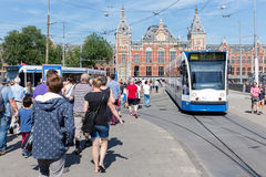 Tourists walking near a tram in Amsterdam Royalty Free Stock Photography