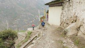 Tourists walking in nepalese village Prok, trek around mountain Manaslu, Nepal.