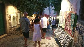 Tourists walking next to displayed souvenirs in Rovinj stock footage