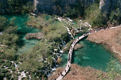 Tourists walking over turquoise water of Plitvice Lakes. royalty free stock image