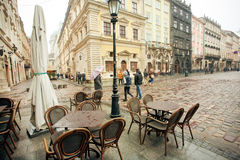 Tourists walking at rainy weather around Market Square with empty outdoor restaurants Royalty Free Stock Image