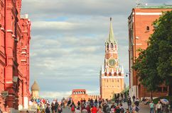 Tourists are walking on Red Square in Moscow. The Kremlin tower with a clock. stock photo