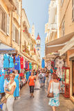 Tourists walking and shopping on narrow streets Stock Images