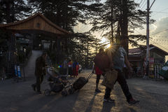 Tourists walking at street of Shimla town with sun flare during sunset. Royalty Free Stock Images