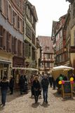 Tourists walking through streets in old mediaval city of Colmar. COLMAR, FRANCE - APRIL 2, 2018: Tourists walking through streets in old mediaval city of Colmar stock photography