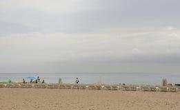 Tourists walking and sunbathing on the beach Stock Image