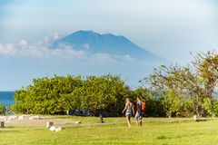Tourists walking to the beach with Mt. Agung in the background stock photos