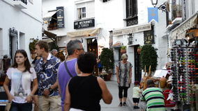 Tourists walking in a typical street village andalusian of Mijas. At sunset stock footage