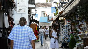 Tourists walking in a typical street village andalusian. Of Mijas at sunset stock footage