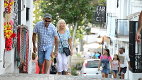 Tourists walking in a typical street village andalusian. Of Mijas at sunset stock video