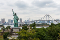 Tourists walking on the walkway view Libety statue and Rainbow bridge in Odaiba Royalty Free Stock Photography