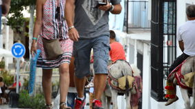 Tourists walking and watching people mounted on a donkey in a typical street of Mijas village in Andalusia. Tourists walking in a typical street village stock video