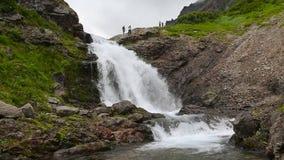 Tourists walks at top of mountain near beautiful waterfall. KAMCHATKA PENINSULA, RUSSIA - July 29, 2016: Group of tourists walks and photographed at top of stock video