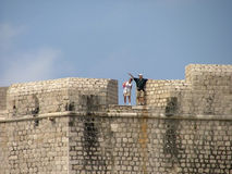 Tourists on wall. A couple of tourists on a fortress wall in Dubrovnik royalty free stock photo