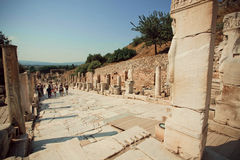 Tourists wallking past alley of Greek-Roman city Ephesus with stone sculptures Royalty Free Stock Image