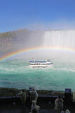 Tourists watch Niagara Falls tour boat under a full rainbow vert Royalty Free Stock Photo