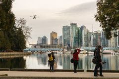 Tourists watch a seaplane in Vancouver harbour Stock Photo